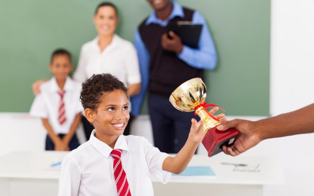 school boy receiving a trophy in classroom